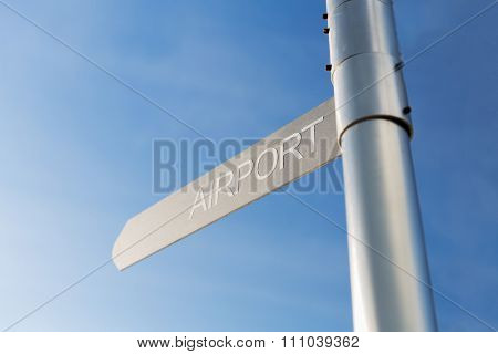 transportation, direction, location, travel and road sign concept - close up of airport signpost over blue sky background