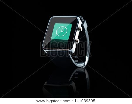 modern technology, time, object and media concept - close up of black smart watch with clock icon on screen over black background