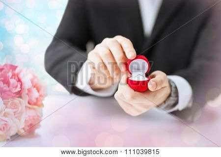 people, holidays, presents and proposal concept - close up of man with gift box and engagement ring over holidays lights background