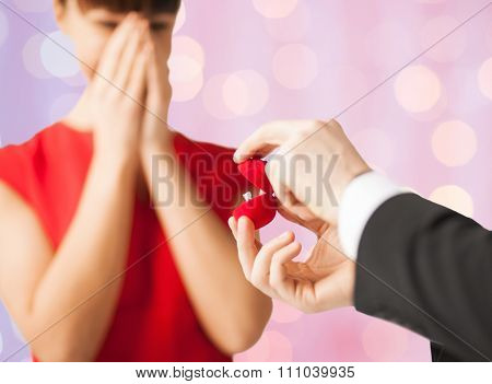 people, proposal, holidays, anniversary and presents concept - close up of couple with diamond engagement ring over holidays lights background