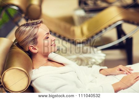 people, beauty, healthy lifestyle and relaxation concept - beautiful young woman lying on chaise-longue in bath robe at spa