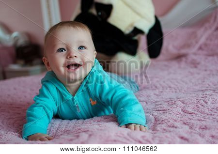 Smiling Baby Lying In Pearent's Bed