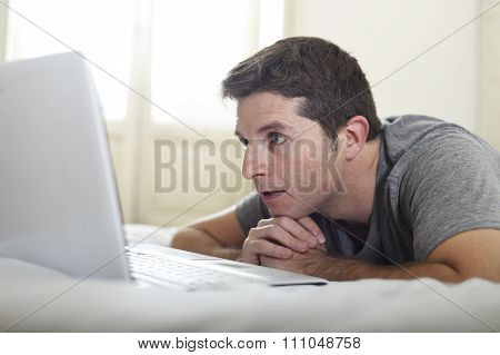 Portrait Of Young Attractive Man Lying On Bed Watching On Line Movie In Computer Laptop At Home In I