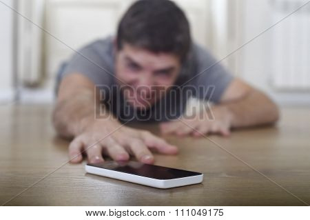 Man Trying To Reach Mobile Phone Creeping On The Ground In Smart Phone And Internet Addiction Concep