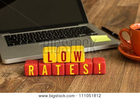 Low Rates! written on a wooden cube in a office desk