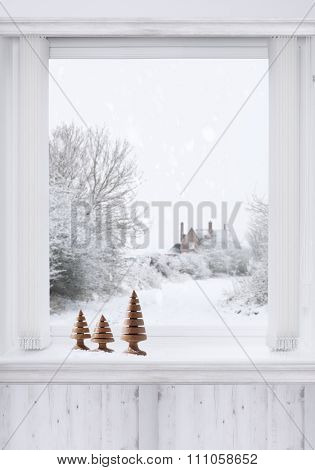 Winter window with turned wooden Christmas trees sitting on the ledge