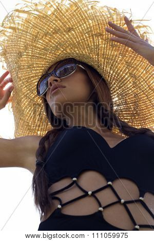 Woman in sunglasses and hat black stylish swimsuit with pigtails poses on roof enjoying landscape vi
