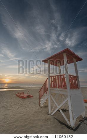 Tower Rescue And Life-raft On A Sandy Beach Sunset