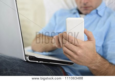 Close Up Hands Of Man Lying On Bed Couch Using Mobile Phone And Computer Working From Home