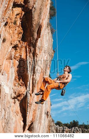 Rock Climber Hanging On Belay Rope Over The Mountains