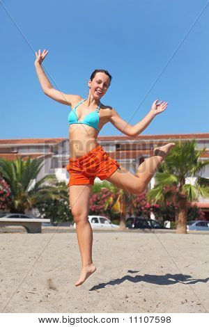 Young Beauty Woman Jumping On Beach And Smiling, House And Palms