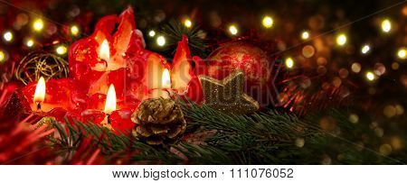 Four red candles with christmas ball and decoration.