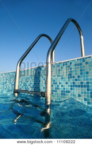 Shiny Chrome Ladder Into Pool, Blue Sky, Blue Water, Blue Bottom