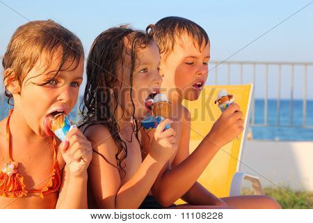 Little Brother And Two Sisters In Swimsuits On Beach Eating Ice Cream After Bath.