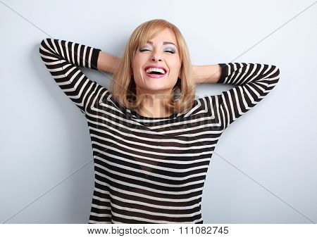 Happy Laughting Blond Woman With Closed Eyes Relaxing Near The Wall
