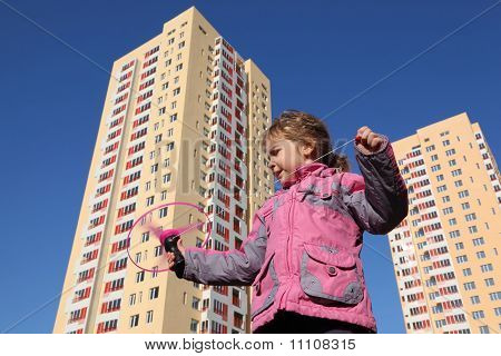 Beautiful Little Girl In Pink Jacket, Plays With Propeller. In Background Of Two High-rise Buildings