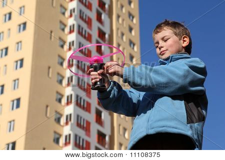Little Boy In Blue Jacket Plays With Pink Propeller. In Background Yellow Multi-storey Building