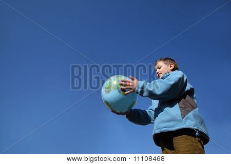Little Boy In Blue Jacket And Brown Pants Holding Balloon In Form Of Globe
