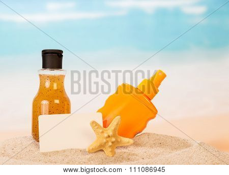 Beach accessories and blank postcard in the sand