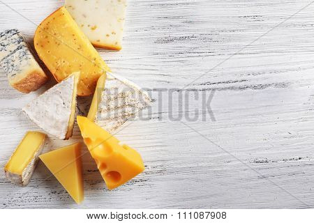 Different kinds of cheese on white wooden background, copy space