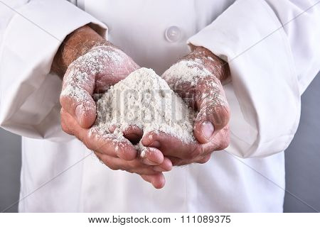 Closeup of a chef holding a two handfuls of flour.