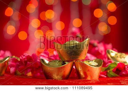 Chinese new year festival decorations, gold ingots and plum flower on red glitter background, copy space on top.