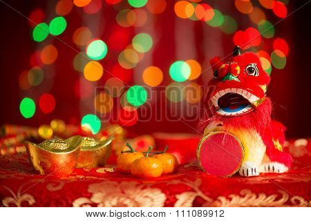 Chinese new year festival decorations, miniature dancing lion and gold ingot on red glitter background.