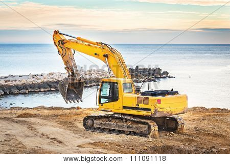 excavator loader machine with sunset background.