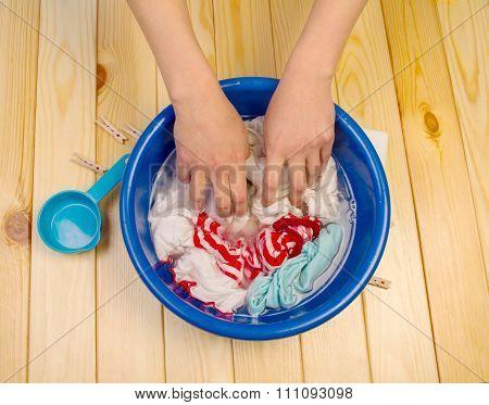 Women's hands wash clothes in blue pelvis