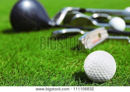 Different golf clubs  and balls on golf course, close up