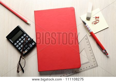 Red notebook with stationery on wooden background
