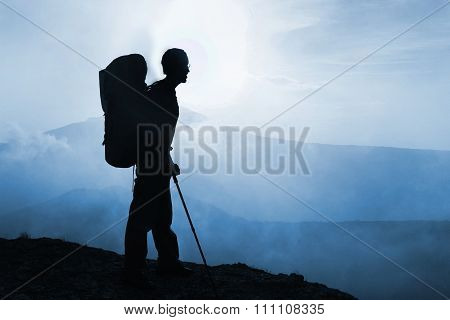 Silhouette Of Man Trekker With Backpack In The Mountains