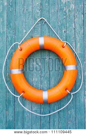 A life buoy on green wooden background