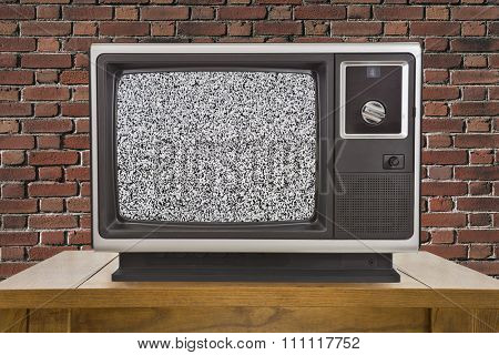 Old television with static screen and brick wall.