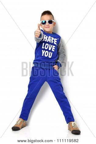 Little Boy In Sunglasses Blue Cloth Jeans Standing And Giving Thumb Up Sign