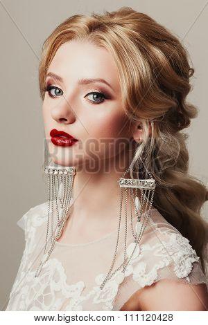 Glamour portrait of a beautiful female model with Shiny long unusual luxury earrings