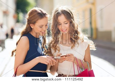 sale, consumerism and people concept - happy young women with shopping bags and smartphone on city street
