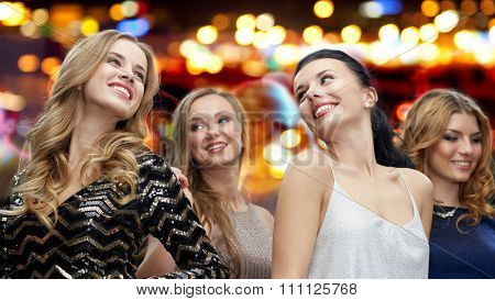 party, holidays, nightlife and people concept - happy young women dancing over night club disco lights background