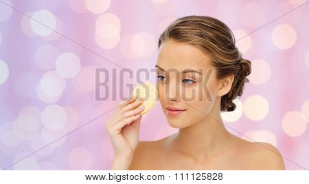 beauty, people and skincare concept - young woman cleaning face with exfoliating sponge over pink holidays lights background