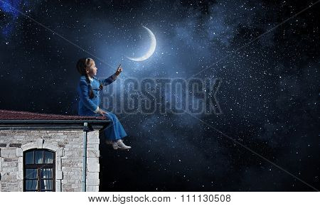 Little girl sitting house roof and pointing with finger on moon
