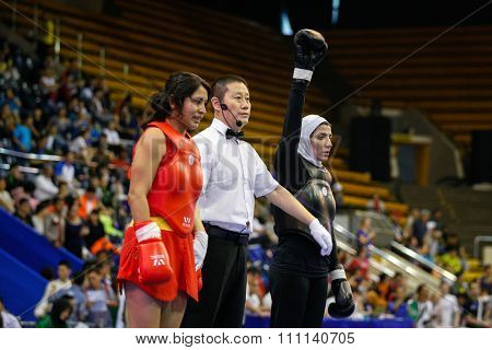 JAKARTA, INDONESIA - NOVEMBER 16, 2015: Gabriel Quintanilla of Peru (red) fights Sedigheh Dariaeivarkadeh of Iran (black) in the women's 60kg Sanda event at the 13th World Wushu Championship 2015.