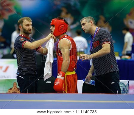 JAKARTA, INDONESIA - NOVEMBER 16, 2015: Ali Magomedov of Russia (red) receives attention from his coaches between rounds during the men's 60kg Sanda event at the 13th World Wushu Championship 2015.