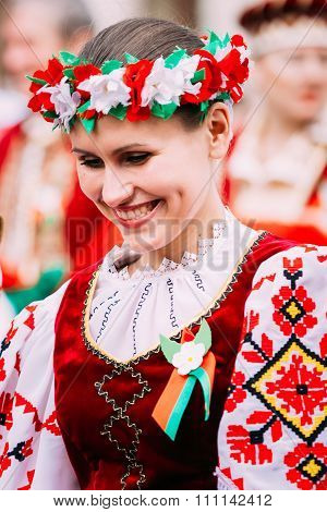 Woman in national Belarusian folk costume participating in the p