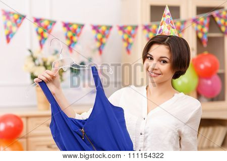 Young girl holding her party dress.