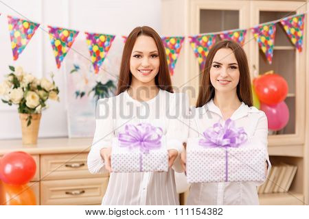 Two young girls are offering presents.