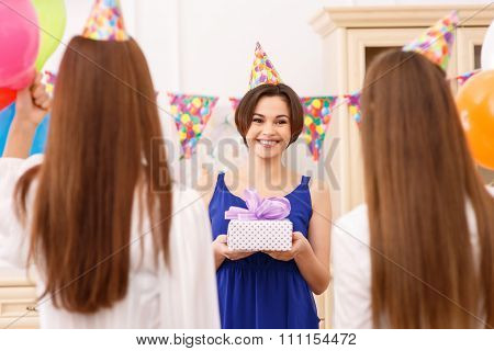 Happy young girl holding a birthday gift