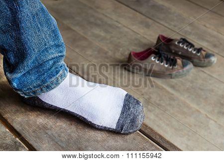 Men Wearing Socks Put A Foot On A Wooden Foor