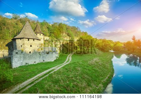 Ancient stone castle in Kamianets Podilskyi standing on hill with green trees and bushes with rural road and river