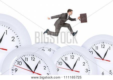Businessman running with set of clocks