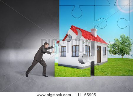 Man pushing puzzle piece of house picture